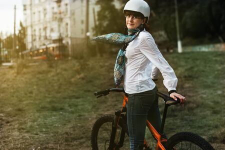 Portrait of happy young bicyclist riding in park on her bike Stock Photo
