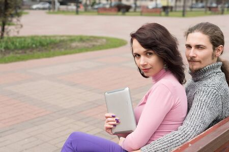 Trendy young couple in town using tablet walking