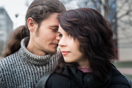 Close up portrait of attractive young couple walking outdoors.