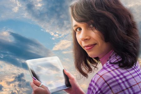 Woman using tablet notebook clouds technology on blue sky background