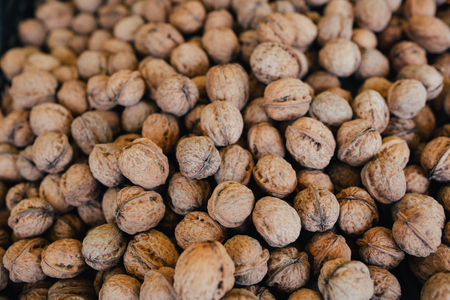 Close-up of walnut background, scattered pile of walnuts on display at the farmers market