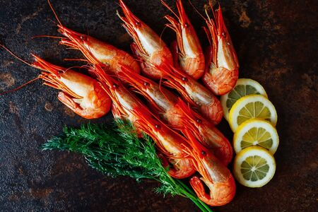 pincers: Shrimps with lemon and greens on a dark background