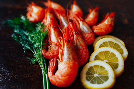 Shrimps with lemon and greens on a dark background