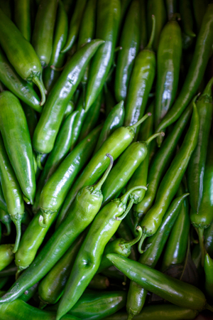 A lot of hot spicy chili green red peppers background