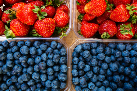Blueberries and strawberries on the market counter