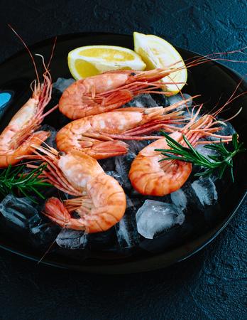Tiger shrimps with lemon, rosemary on stone background. Фото со стока