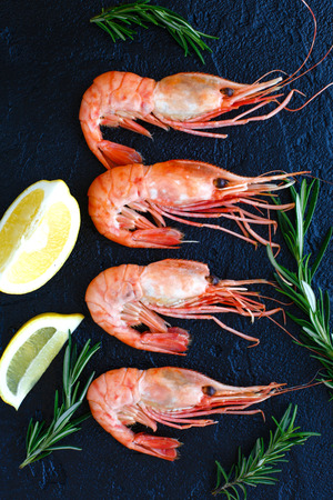 Shrimps with lemon and rosemary on a dark background