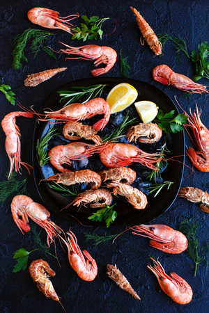 Tiger shrimps with lemon, rosemary on stone background. Banque d'images