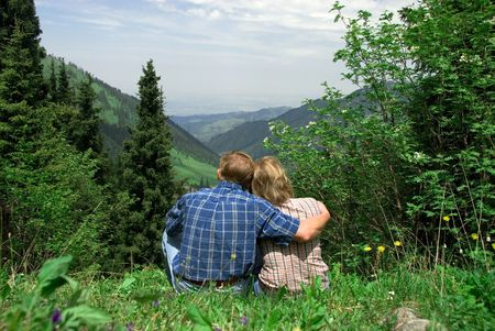 Rear view image of a cute mature couple sitting outdoors in mountain