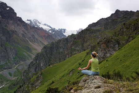 The young girl makes meditation in beautiful mountain gorge. Snow tops are in the distance visible photo