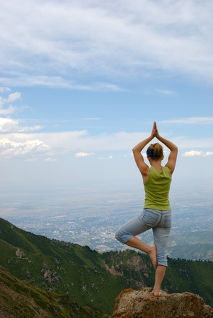The young girl in a yoga position  stands at edge of a rock