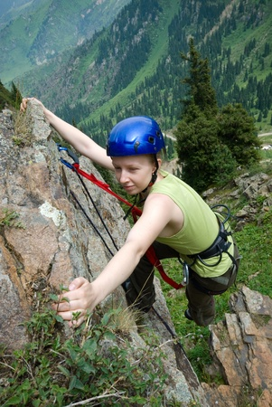 The girl the climber trains on a rock in beautiful mountain gorge photo