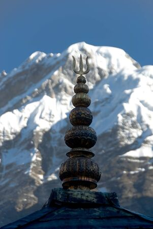 Top of a roof of a monastery against the Himalaya mountains  A trident a symbol of the God Shiva