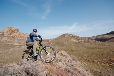 Bicyclist in mountain terrain overcomes obstacle