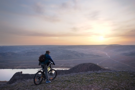 Bicyclist looks at beautiful sundown in steppe photo