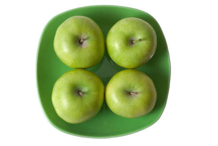 Four green apples on green plate on white background