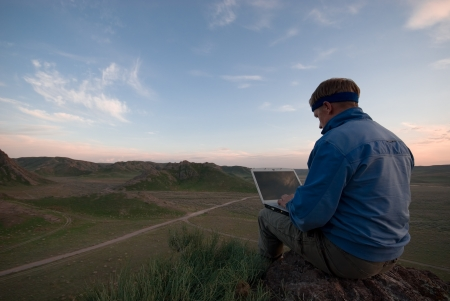 The man with the laptop sits on a hill against the evening sky Stock Photo