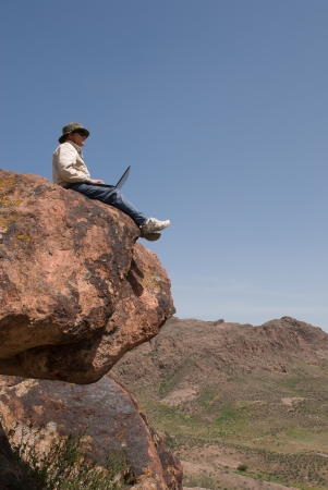 Man with the laptop sits on the brink of breakage  Vertical frame Stock Photo