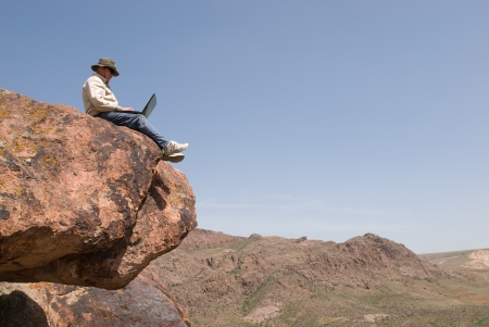 Man with the laptop sits on the brink of breakage  Horizontal frame photo