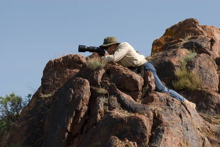 Photographer takes pictures hiding among rocks