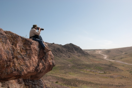 Photographer takes pictures sitting on the big hanging stone photo