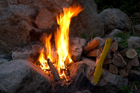 Campfire amongst stone, late in wood at night