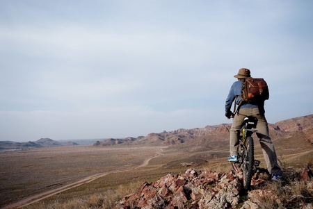 Bicyclist in hilly terrain looks at road