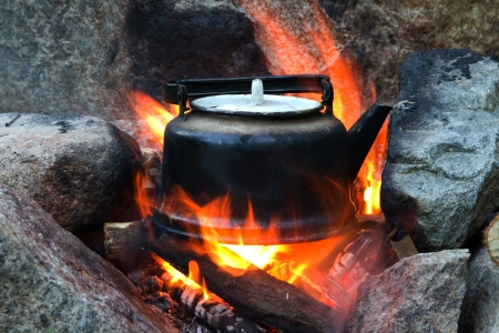 Old teapot boils on campfires photo