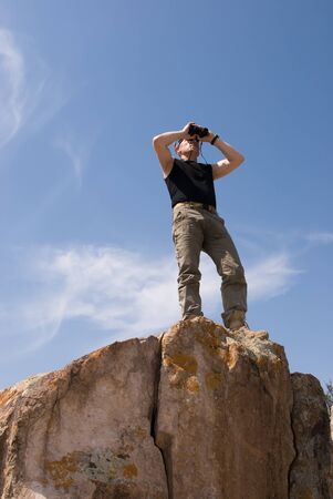 The man at top of a rock on background sky and looks into binoculars