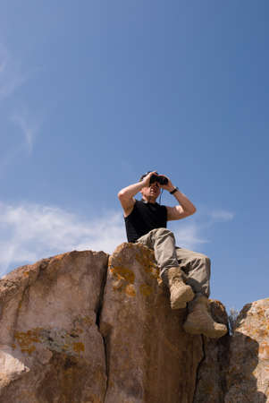 The man sits at top of a rock on background sky and looks into binoculars
