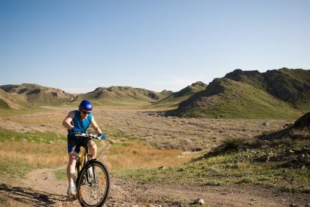 Mountain bicyclist in beautiful wild terrain