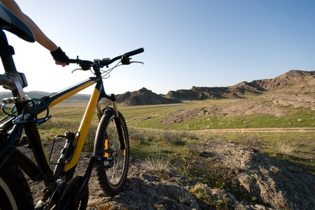 Bicycle in a hilly valley shined with the evening sun Stock Photo