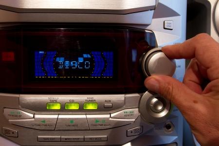 The close up, hand adjusts a radio receiver