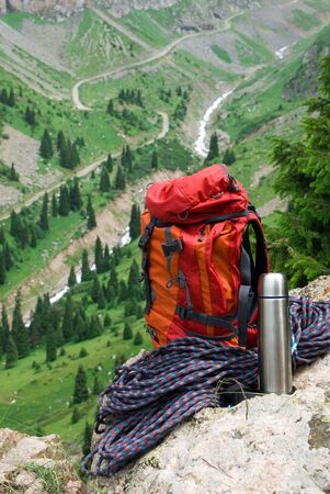 Rucksack, rope and thermos on background of the mountain road