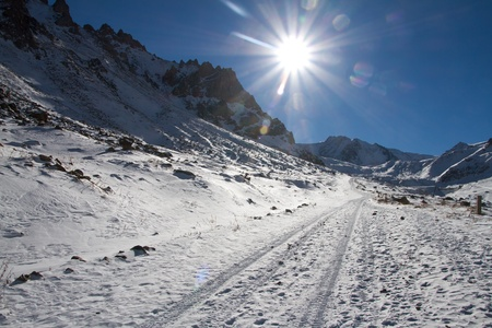 Mountain road shined with the bright sun, natural patches of light