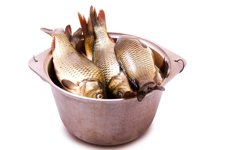 Fresh fish in a cast-iron kettle on a white background Stock Photo