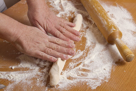 hands of the baker rolling dough for pizza Stock Photo