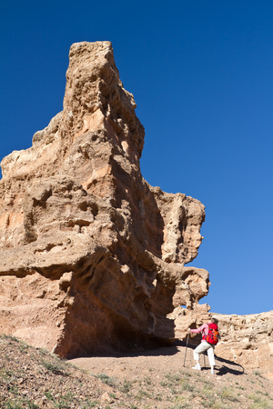 The woman with a backpack looks at fantastical rocks Stock Photo