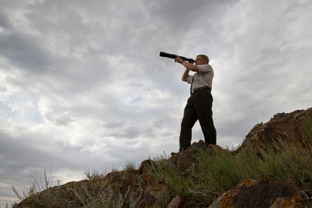 next horizon: The businessman looks in a telescope against the storm sky Stock Photo