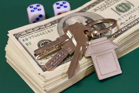keys money and rolling dice on a green table, selective focus