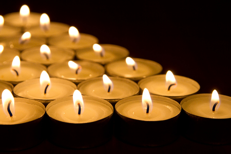 many tea light candles in the dark, close-up Stock Photo