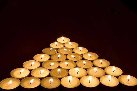 burning candles in the shape of a pyramid, closeup