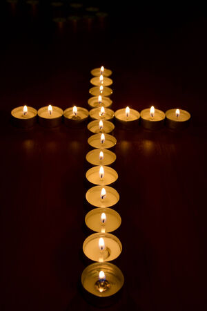 burning candles in the shape of a cross, selective focus Stock Photo