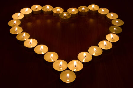 burning candles in the shape of heart, selective focus