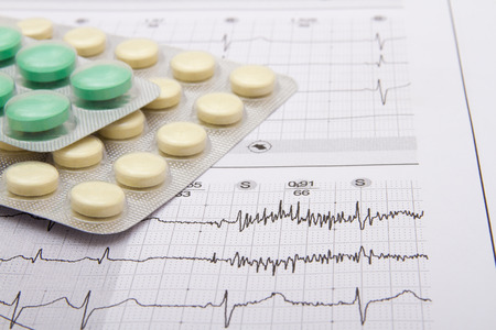 pack of pills on top of ECG, close-up