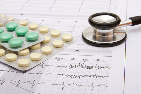 pack of pills and stethoscope on top of ECG, close-up