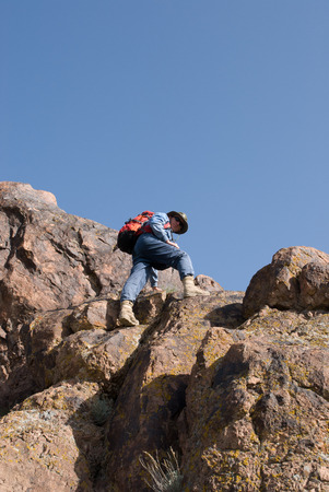 Mountaineer with backpack stands high on a rock and looking down