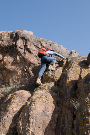 Mountaineer with backpack climbs to the top of the cliff