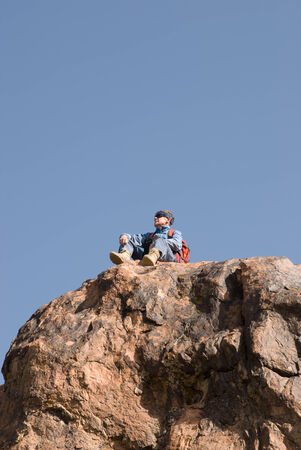 Mountaineer with backpack sitting on top of a rock and looking around Stock Photo