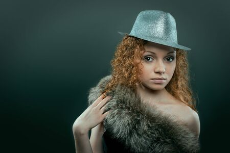 silver fox: Beauty young woman in hat and fur studio shot